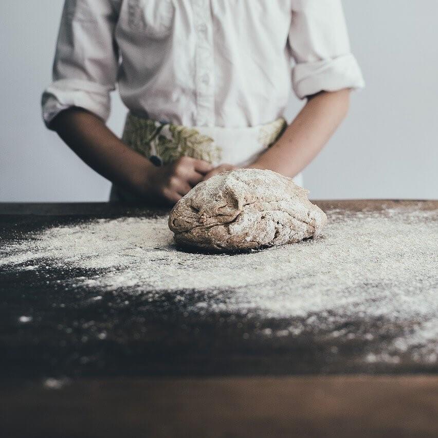 Foto di un impasto cosparso di farina appoggiato al centro di un tavolo di legno grezzo. Mezzo busto della cuoca sullo sfondo.