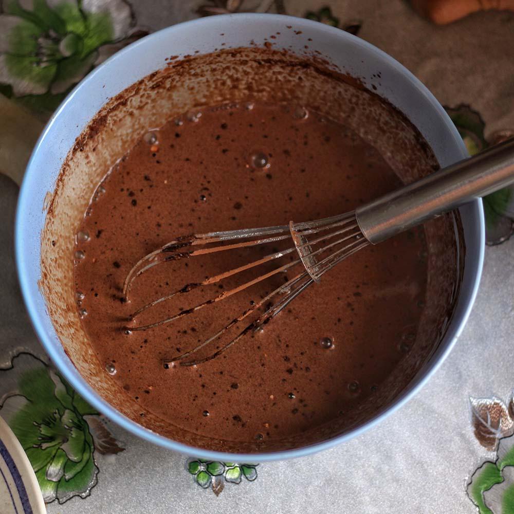 Tazza di cioccolata calda in tazzina vintage, accompagnata da biscotti con gocce di cioccolato.