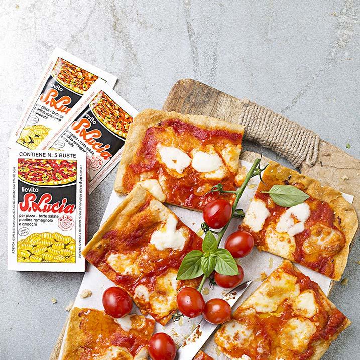 Tagliere con pizza margherita tagliata a quadretti, decorata con pomodorini e basilico. Accanto, packaging e bustine di lievito Santa Lucia. Foto dall'alto.